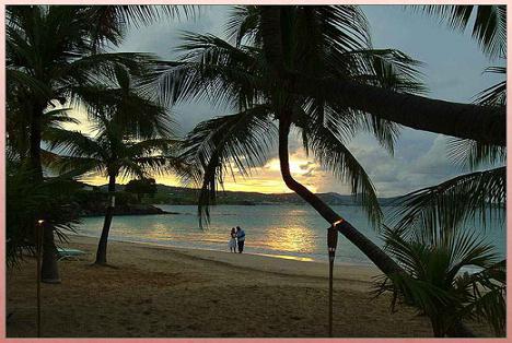 A Couple Taking A Romantic Stroll On A Beautiful Beach.
